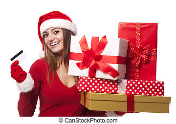 Woman wearing santa hat holding christmas gifts and credit card