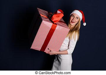 Woman wearing santa hat holding christmas gifts