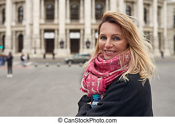 Woman wearing scarf in front of historic building