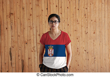 Woman wearing Serbia flag color shirt and standing with two hands in pant pockets on the wooden wall background, a horizontal tricolor of red blue and white; charged with the lesser Coat of arms.