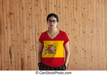 Woman wearing Spain flag color shirt and standing with two hands in pant pockets on the wooden wall background, a horizontal of red yellow and red; charged with the Spanish coat of arms.