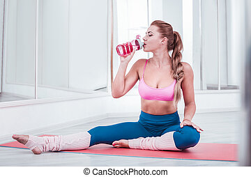 Woman wearing sportswear drinking some water after intensive training
