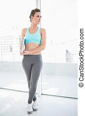 Woman wearing sportswear holding laptop