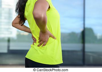 Woman wearing sportswear holding painful back - Woman...