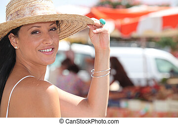 Woman wearing straw hat stood by outdoor market