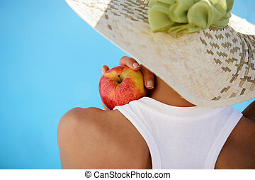 woman wearing summer hat and holding an apple
