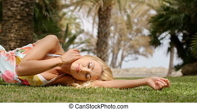 Woman Wearing Sun Dress Lying on Side on Grass