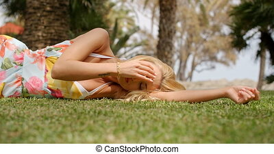 Woman Wearing Sun Dress Lying on Side on Grass