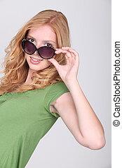 Woman wearing sunglasses in studio