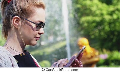 Woman wearing sunglasses in the park with a smartphone. A woman is writing a message on her mobile phone on blurred fountain on a background. Slow motion. 1920x1080, hd