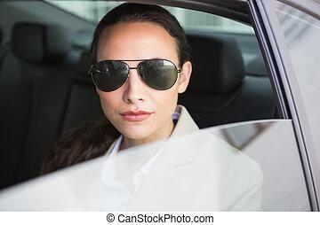 Woman wearing sunglasses looking at camera