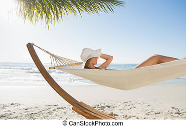 Woman wearing sunhat and bikini relaxing on hammock at the beach