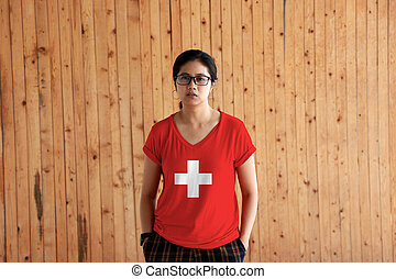 Woman wearing Switzerland flag color shirt and standing with two hands in pant pockets on the wooden wall background.