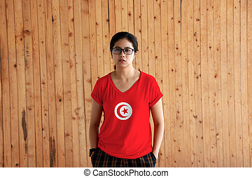 Woman wearing Tunisia flag color shirt and standing with two hands in pant pockets on the wooden wall background.