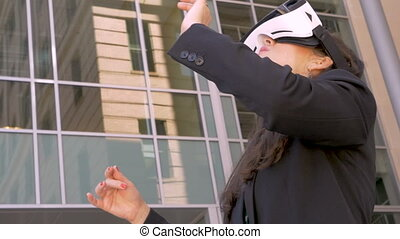 Woman wearing VR goggles experiencing virtual reality outside glass building