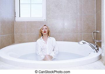 Woman wearing white shirt relaxing in the bath