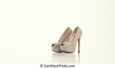 woman wears beige shoes with high heels - the woman wears...