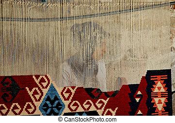 Woman weaves a Turkish carpet