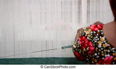Woman weaving a rug on a loom