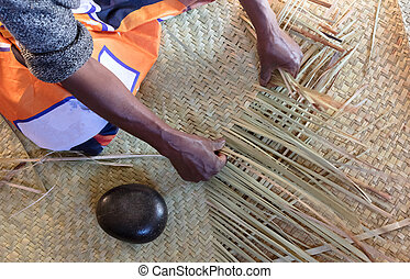 Woman weaving rug out of grass reeds
