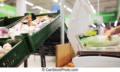 woman weighing chinese cabbage on scale at grocery -...