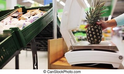 woman weighing pineapple on scale at grocery store -...