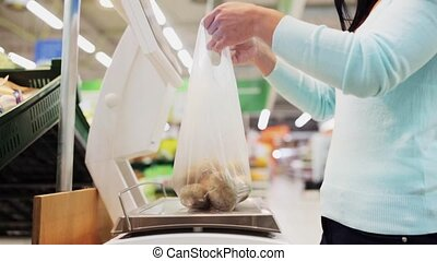 woman weighing potato on scale at grocery store - shopping,...