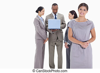 Woman welcoming and co-workers with a laptop in the background