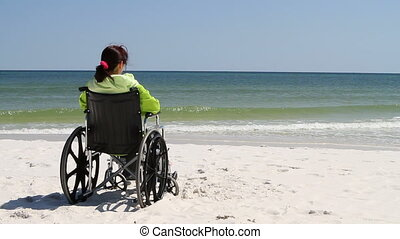Woman Wheelchair Beach - Disabled woman sitting in a...