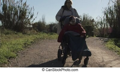woman wheeling a child with multiple physical and intellectual disabilities, with reduced mobility, on a dirt road, on a path. they are dressed in gray and red anoracs.