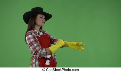 woman while cleaning makes gestures like a cowboy with gun against green screen.