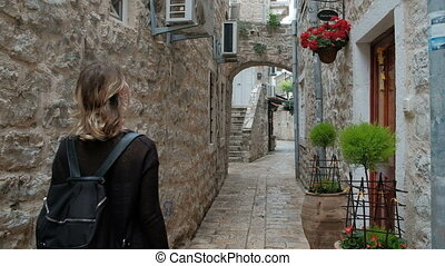 Woman while traveling with interest looks at narrow streets....
