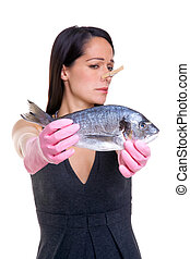 Woman who doesn't like fish - A woman holding a fish at arms...