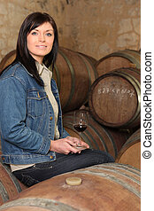 Woman wine tasting in a cellar