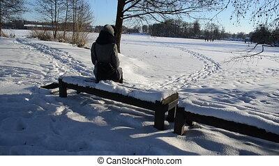 woman winter admire lake - woman in grey coat sit on wooden...