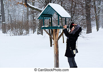 Woman winter feeding birds