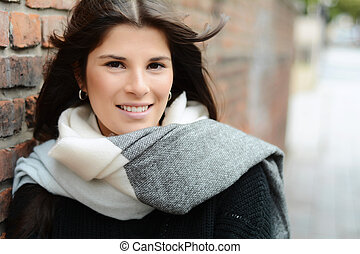 Woman winter portrait against a brick wall.