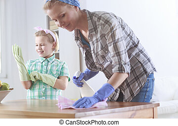 Woman wiping a table and her daughter helping her