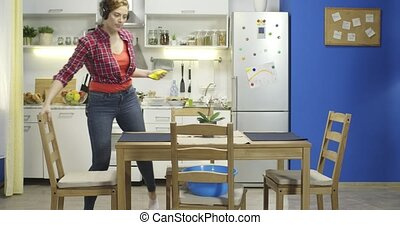 Woman wiping dust and cleaning her kitchen.