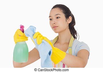 Woman wiping surface with cloth wearing apron and rubber...
