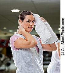 Woman Wiping Sweat With Towel At Health Club - Portrait of...