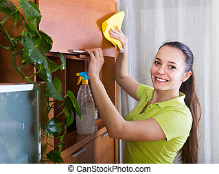 Woman wiping the dust from furniture