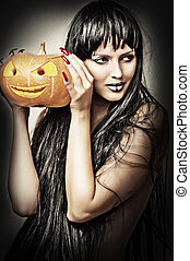 Woman witch holding pumpkin