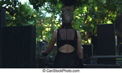 Woman witch standing in the cemetery. An old-fashioned...