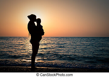 Woman with a baby on hands at sunset