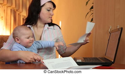 reading some financial notice - Woman with a baby on hands...