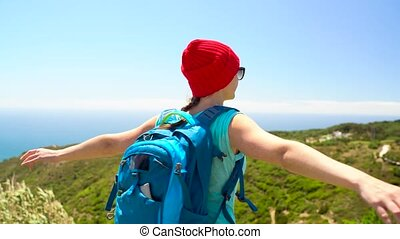 Woman with a backpack behind her back is spinning her arms out to the sides, standing on top of a hill on the ocean shore