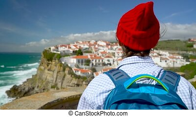 Woman with a backpack enjoys a view of the ocean coast near Azenhas do Mar, Portugal