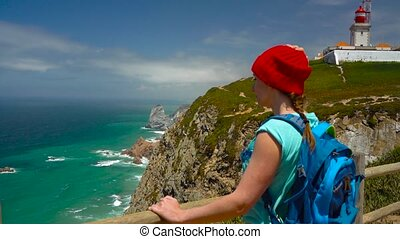 Woman with a backpack enjoys a view of the ocean coast near the lighthouse