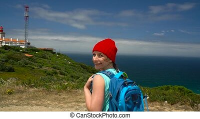 Woman with a backpack goes on a picturesque hilly terrain to the lighthouse near the ocean
